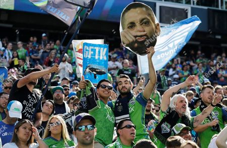 A fan in the supporters section holds a photo of Seattle Sounders forward Clint Dempsey, who announced his retirement from professional soccer earlier in the week, and was honored during a ceremony before an MLS soccer match between the Sounders and Sporting Kansas City, in Seattle. The Sounders won 3-1