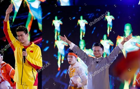 Chinese swimmer Sun Yang, left, waves on stage with Jack Ma executive chairman of Alibaba Group during the closing ceremony for the 18th Asian Games in Jakarta, Indonesia