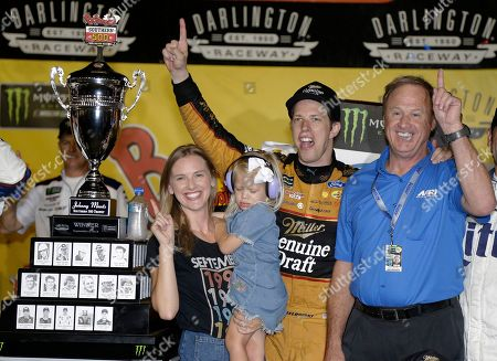 Brad Keselowski celebrates with his wife, Paige; daughter, Scarlett; and former Team Penske driver Rusty Wallace, right, in Victory Lane after winning the NASCAR Cup Series auto race at Darlington Raceway, in Darlington, S.C