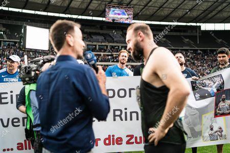 Berlin, Deutschland, 02.09.2018: Robert Harting nach seinem letzten Wurf bei seinem letzten Wettkampf im TV Interview unter Beobachtung von seinem Bruder Christoph beim Leichtathletik Meeting ISTAF im Berliner Olympiastadion.