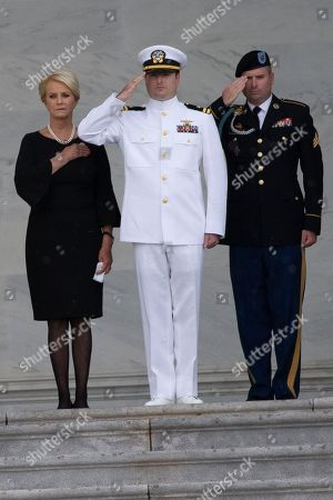 Stock Picture of Cindy McCain and her sons Jack McCain, center, and Jimmy McCain, right, stand at attention as a United States Military Honor Guard carries the casket of former Senator John McCain, Republican of Arizona, up the stairs of the Capitol in Washington, DC in Washington, DC. McCain, a United States Military veteran and longtime Senator, will lay in state inside the Capitol Rotunda for one day prior to being laid to rest on September 1, 2018 at the United States Naval Academy in Annapolis, Maryland.