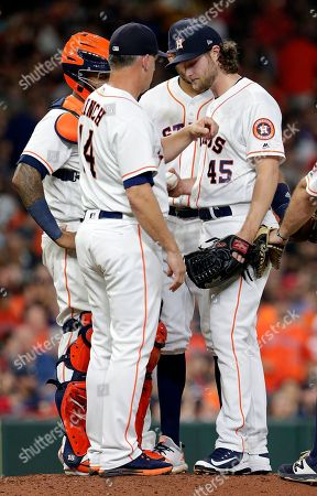 Houston Astros manager AJ Hinch (14) pulls starting pitcher Gerrit Cole (45) with two runners on base and two out in the sixth inning of a baseball game against the Los Angeles Angels, in Houston