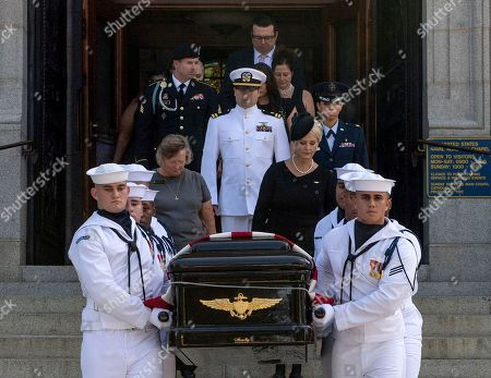 In this image provided by the U.S. Navy, Navy Body Bearers walk with the casket of Sen. John McCain, R-Ariz., followed by family members including Cindy McCain, to place it onto a horse-drawn caisson after his funeral service at the United States Naval Academy Chapel, in Annapolis, Md. McCain was buried in the cemetery at the Naval Academy