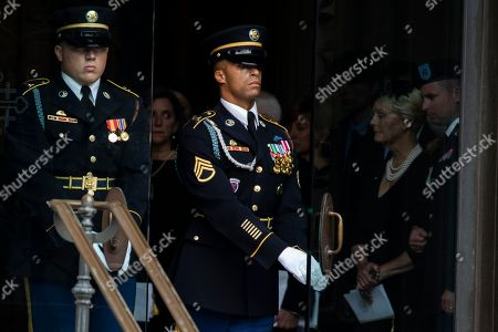 Stock Picture of Cindy and Jimmy McCain, right, the wife and son of late United States Senator John McCain (Republican of Arizona) look on as a Military Honor Guard carries the Senator's casket out of the Cathedral following a funeral for the late Senator at the Washington National Cathedral in Washington, DC.