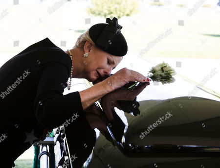 In this hand-out photo released by the McCain family, Cindy McCain lays her head on the casket of Senator John McCain, R-Ariz., during a burial service at the cemetery at the United States Naval Academy in Annapolis, Md.,.