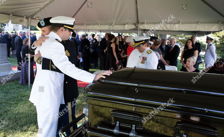 In this hand-out photo released by the McCain family, Jimmy McCain hugs his brother Jack McCain, touching casket, as Cindy McCain, watches during a burial service for Senator John McCain, R-Ariz.,at the cemetery at the United States Naval Academy in Annapolis, Md.