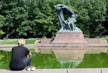 A tourist sits by the Chopin monument in Lazienki park in Warsaw, Poland, . The world's first Frederic Chopin piano competition on instruments from his era has opened in Warsaw with the goal of reviving the sound and the technique of the music as it was written by the Polish-born composer in the 19th century