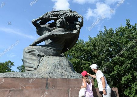 Tourists admire the Chopin monument in Lazienki park in Warsaw, Poland, . The world's first Frederic Chopin piano competition on instruments from his era has opened in Warsaw with the goal of reviving the sound and the technique of the music as it was written by the Polish-born composer in the 19th century