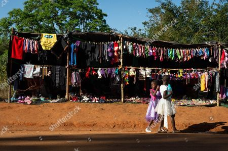 Young girls pass by stands selling underwear near the Swazi Royal Residence with their reeds to be presented to King Mswati III, Mbabane, Swaziland, 03 September 2018.  On the main day of the eight-day event, the young women gather in their groups according to where they live and present the reeds to the Queen Mother and King Mswati III as a rite of passage.