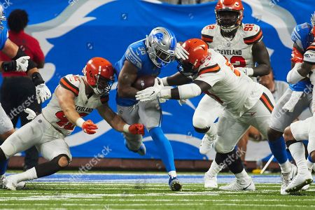 Detroit Lions running back Dwayne Washington (36) is tackled by Cleveland Browns linebacker Justin Currie (42) and defensive tackle Jeremy Faulk (97) during an NFL football game at Ford Field in Detroit