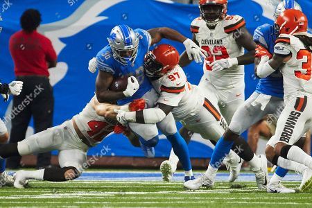 Stock Photo of Detroit Lions running back Dwayne Washington (36) is tackled by Cleveland Browns linebacker Justin Currie (42) and defensive tackle Jeremy Faulk (97) during an NFL football game at Ford Field in Detroit