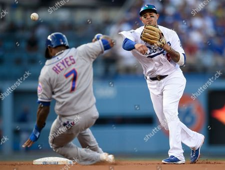 Los Angeles Dodgers shortstop Manny Machado, right, throws to first after forcing out New York Mets' Jose Reyes to complete a double play during the fifth inning of a baseball game in Los Angeles, . Jeff McNeil was forced out at first base