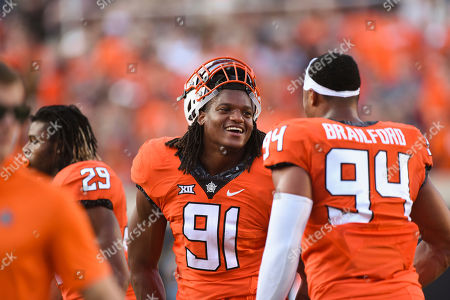 James Washington. Oklahoma State defensive end Mike Scott (91) talks with fellow defensive end Jordan Brailford (94) before a college football game in Stillwater, Okla