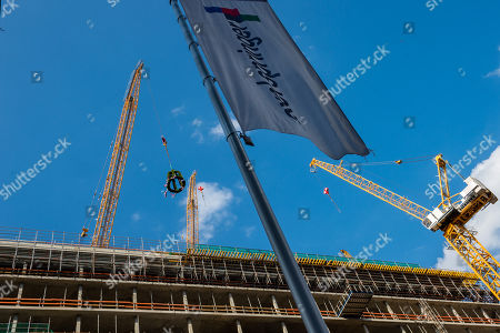 Stock Photo of The ring is fixed to a crane during the topping out of the new Axel Springer building in Berlin, Germany, 04 September 2018. The new building of Axel Springer, one of the biggest digital publishers in Europe that owns various multimedia news brands is designed by Dutch architect Rem Koolhaas.
