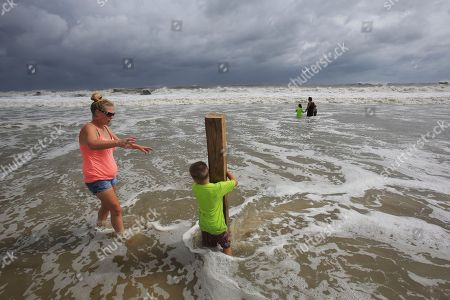 Lauren Dueitt, left, and John Payne, 6, right, play in the high tide waters caused by Tropical Storm Gordon, in Dauphin Island, Ala