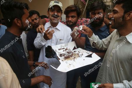 Supporters of Tehreek-e-Insaf headed by Imran Khan, share cake to celebrate the success of their leader elected president of Pakistan, in Karachi, Pakistan, . Pakistani lawmakers elected a nominee from Khan's party to the ceremonial office of president on Tuesday, further cementing its hold on power. Arif Alvi will replace President Mamnoon Hussain, who completes his five-year term on Sept. 9. Pakistan's elections oversight body will certify the result Wednesday