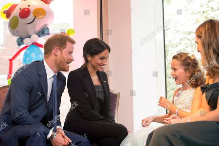Britain's Prince Harry, left, the patron of the charity WellChild and his wife Meghan Duchess of Sussex with Chloe Henderson and her sister Hana at the annual WellChild Awards at the Royal Lancaster Hotel in London,. The couple attended the annual WellChild awards Tuesday for the charity, who help to get seriously ill children and young people out of hospital and home to their families