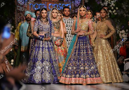 Models present traditional Pakistani dress designed by Nomi Ansari during a fashion parade arranged by the Loreal Paris Pakistan Fashion Design Council in Lahore, Pakistan