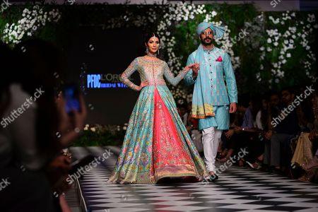 Models present traditional Pakistani dress designed by Nomi Ansari during a fashion show arranged by the Loreal Paris Pakistan Fashion Design Council in Lahore, Pakistan