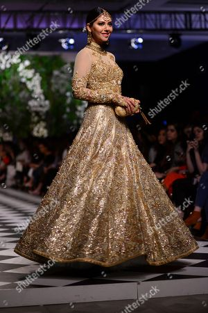 A model presents traditional Pakistani dress designed by Nomi Ansari during a fashion show arranged by the Loreal Paris Pakistan Fashion Design Council in Lahore, Pakistan