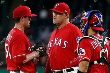 Jeffrey Springs, Doug Brocail, Robinson Chirinos. Texas Rangers starting pitcher Jeffrey Springs is checked by pitching coach Doug Brocail and catcher Robinson Chorines (61) during the second inning of a baseball game against the Los Angeles Angels, in Arlington, Texas