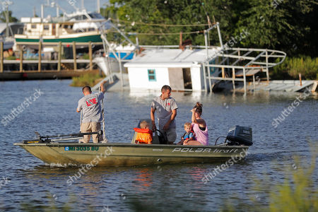Aaron Seal, left, and Mark Mayo, standing center, go check on their boat moorings with family members, in preparation for Tropical Storm Gordon, expected to make landfall as a hurricane this evening, in Pass Christian, Miss., . Behind them is a boat that sunk from last year's Hurricane Nate