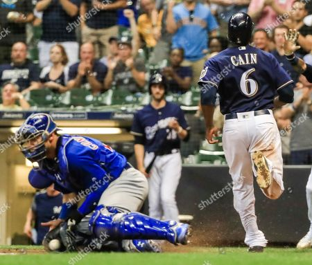 Milwaukee Brewers center fielder Lorenzo Cain (R) scores on a double hit by Milwaukee Brewers right fielder Christian Yelich as Chicago Cubs catcher Willson Contreras (L) of Venezuela takes the throw from the outfield in the seventh inning of the MLB game between the Chicago Cubs at Milwaukee Brewers at Miller Park in Milwaukee, Wisconsin, USA, 04 September 2018.