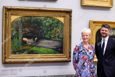 """Maria Balshaw, Director of Tate, and Nick Mitzevich, Director of the National Gallery of Australia, pose with """"Ophelia"""", 1851-52, by John Everett Millais, at Tate Britain, to mark the launch of a major new exhibition at the National Gallery of Australia (NGA) in December 2018."""