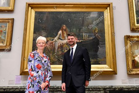 """Maria Balshaw, Director of Tate, and Nick Mitzevich, Director of the National Gallery of Australia, pose with """"The Lady of Shalott"""", 1888, by John William Waterhouse, at Tate Britain, to mark the launch of a major new exhibition at the National Gallery of Australia (NGA) in December 2018."""