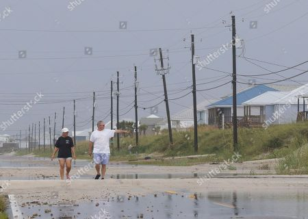 Susan and Bill Jones walk through a road partially covered with sand from Tropical Storm Gordon, in Dauphin Island, Ala