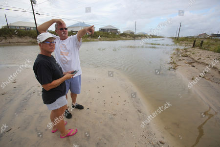 Stock Picture of Susan and Bill Jones check their neighbor's homes while walking the sand and water covered streets from Tropical Storm Gordon, in Dauphin Island, Ala