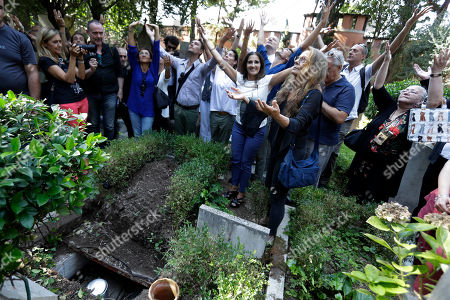 Mourners gather around the tomb where the urn containing Lindsay Kemp's ashes was buried, at the non-catholic cemetery, in Rome . Influential British dancer, choreographer and mime artist Lindsay Kemp, known for tutoring singers David Bowie and Kate Bush during his career, died Aug. 24 at his home in Leghorn, Tuscany, he was 80