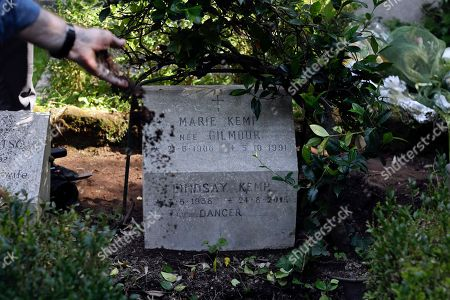 Stock Picture of A man casts soil over the tomb where the urn containing Lindsay Kemp's ashes was buried, at the non-catholic cemetery in Rome . Influential British dancer, choreographer and mime artist Lindsay Kemp, known for tutoring singers David Bowie and Kate Bush during his career, died Aug. 24 at his home in Leghorn, Tuscany, he was 80