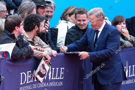 US novelist John Grisham signs autographs as he