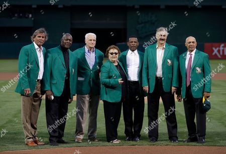 """Dennis Eckersley, from left, Dave Stewart, Paul Finley, representing his late father Charlie Finley, Helen Hunter, representing her late husband Jim """"Catfish"""" Hunter, Rickey Henderson, Rollie Fingers and Reggie Jackson pose for photos at a ceremony for the inaugural class of the Oakland Athletics team Hall of Fame before a baseball game between the Athletics and the New York Yankees in Oakland, Calif"""