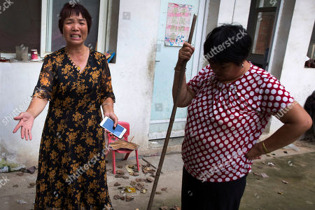 "Xu Ying, left, stands with her neighbor at their home in Gucheng village in central China's Henan province. The AP spoke to the family Marip Lu, a young woman from Myanmar, accused of abusing her. The father, Li Qinggong, and mother, Xu Ying, (pictured) both denied Marip Lu had been abused or raped, and insisted she had not been purchased. But neither was able to explain how she'd ended up in their faraway village, or how she allegedly met and ""married"" their mentally disabled son, Li Mingming"