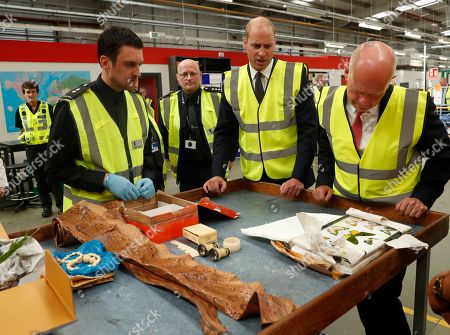 Stock Image of Britain's Prince William watches as a UK Border Force shows off various items found recently, including snake skin, ivory and plants that are not allowed into Britain, during a visit to the Royal Mail international distribution centre near Heathrow airport in Slough, England