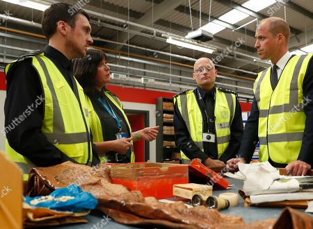 Britain's Prince William watches as a UK Border Force shows off various items found recently, including snake skin, ivory and plants that are not allowed into Britain, during a visit to the Royal Mail international distribution centre near Heathrow airport in Slough, England