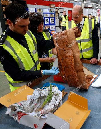 Stock Picture of Britain's Prince William watches as a UK Border Force shows off various items found recently, including snake skin, ivory and plants that are not allowed into Britain, during a visit to the Royal Mail international distribution centre near Heathrow airport in Slough, England