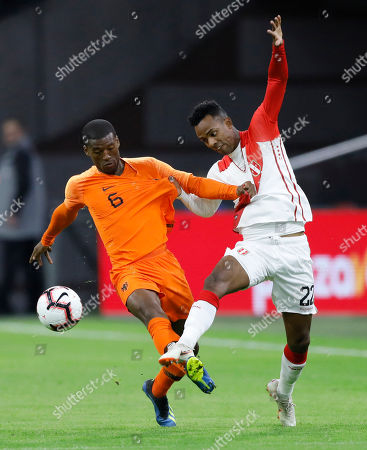 Georginio Wijnaldum of The Netherlands, left, and Peru's Nilson Loyola vie for the ball during the international friendly soccer match between The Netherlands and Peru at the Johan Cruijff ArenA in Amsterdam, Netherlands