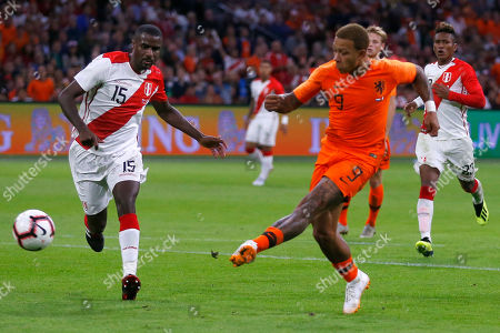Memphis Depay of The Netherlands, right, scores 1-1, before Peru's Christian Ramos can block the shot during the international friendly soccer match between The Netherlands and Peru at the Johan Cruijff ArenA in Amsterdam, Netherlands