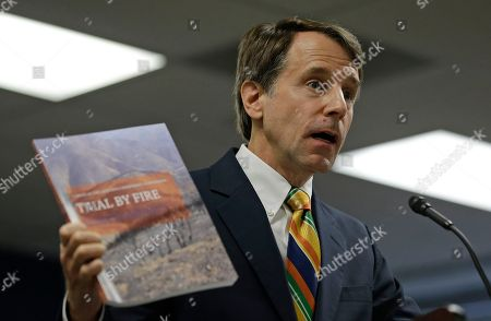 Stock Image of California Insurance Commissioner Dave Jones holds up a copy of a report during a news conference about the costs of recent wildfires, in San Francisco. Jones released the first data on the total insurance claims reported for residential and commercial losses following the Carr and Mendocino Complex wildfires. Commissioner Jones also released updated data for the 2017 California wildfires and 2018 mudslides