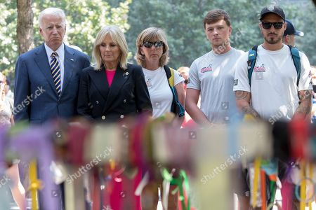 Joe Biden, Jill Biden. Former Vice President Joe Biden, left, and his wife Dr. Jill Biden, second from left, stand with members of Walking With The Wounded during a moment of silence after laying a wreath at the Survivor Tree at the 9/11 memorial as they complete the 1,000-mile Walk of America, in New York