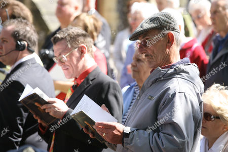 Members of the public read the order of service at the funeral for the late First World War veteran and world's oldest man, Henry Allingham