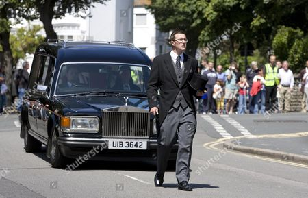 The hearse carring Henry Allingham's coffin is taken from St Nicholas Church in Brighton.
