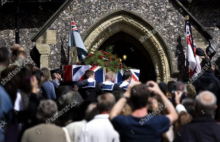 The coffin containing the body of Henry Allingham is carried into the church by a joint Royal Navy and Royal Air Force bearer party