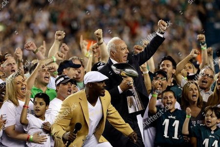 Philadelphia Eagles' Jeffrey Lurie reacts alongside Brian Dawkins during a ceremony before an NFL football game against the Atlanta Falcons, in Philadelphia