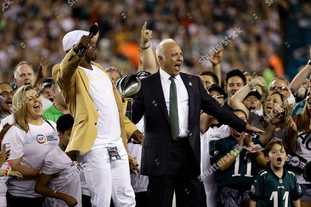 Philadelphia Eagles owner Jeffrey Lurie reacts alongside Brian Dawkins during a ceremony before the team's NFL football game against the Atlanta Falcons, in Philadelphia