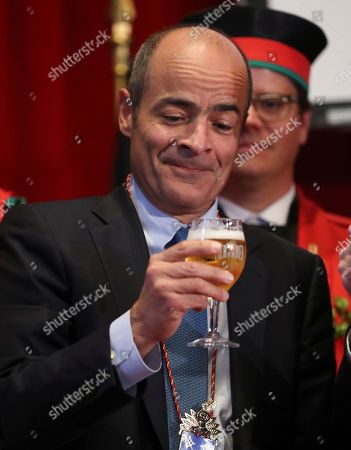 Brazilian Carlos Brito (C), CEO of the world's largest brewery company Anheuser-Busch InBev., looks at a glass of beer as he along with other official guests attends the opening of the 20th edition of the Belgian Beer Weekend in downtown Brussels, Belgium, 07 September 2018. Others are not identified. Brito and the Belgium Prime Minister Charles Michel (unseen) were both enthroned as 'Chevaliers' during a ceremony. More that 400 kinds of beers are presented during this events.