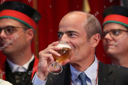 Brazilian Carlos Brito (C), CEO of the world's largest brewery company Anheuser-Busch InBev., drinks from a glass of beer as he along with other official guests attends the opening of the 20th edition of the Belgian Beer Weekend in downtown Brussels, Belgium, 07 September 2018. Others are not identified. Brito and the Belgium Prime Minister Charles Michel (unseen) were both enthroned as 'Chevaliers' during a ceremony. More that 400 kinds of beers are presented during this events.